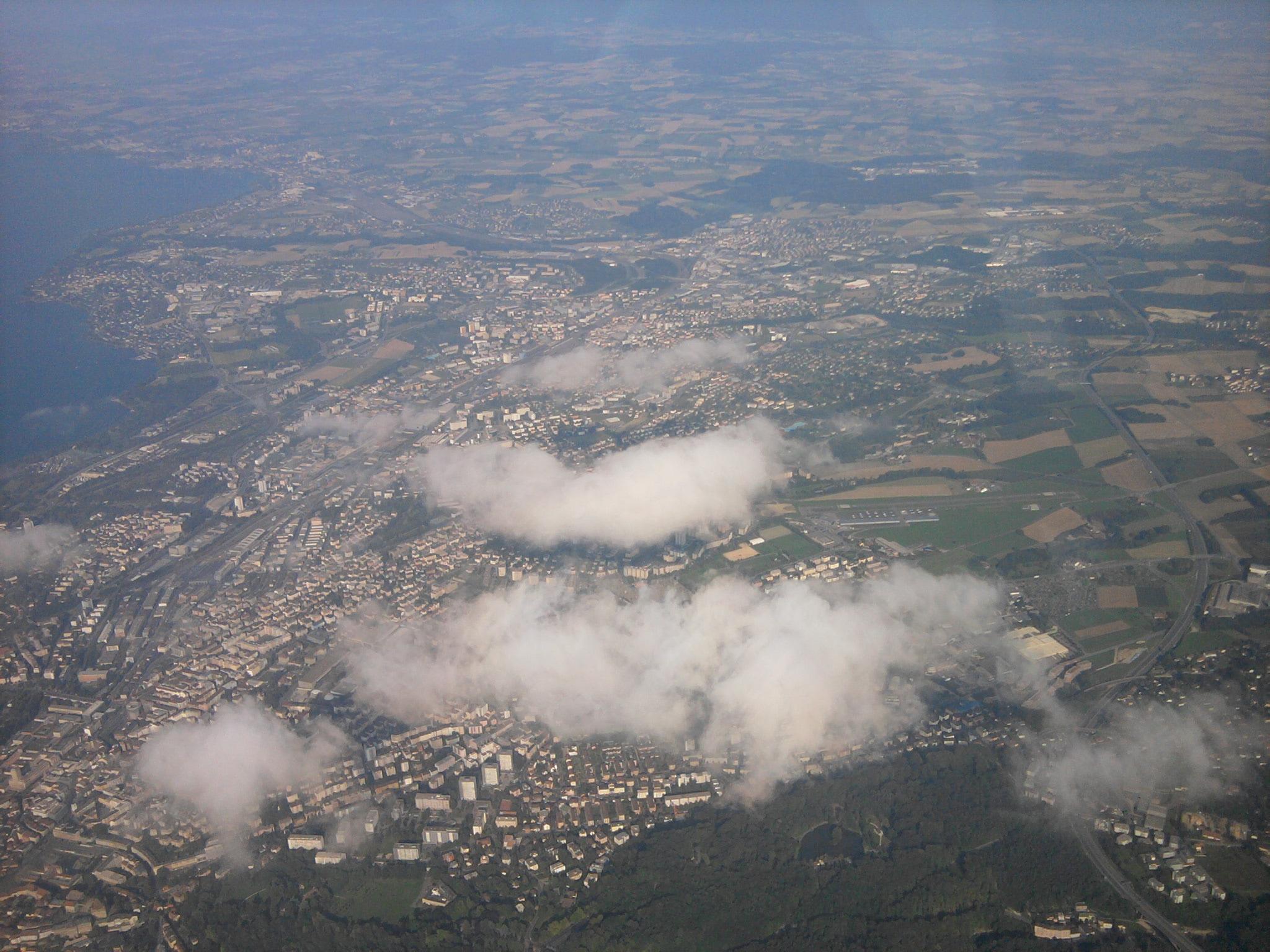 Lausanne. On aperçoit la terrain de la ville entre les nuages.