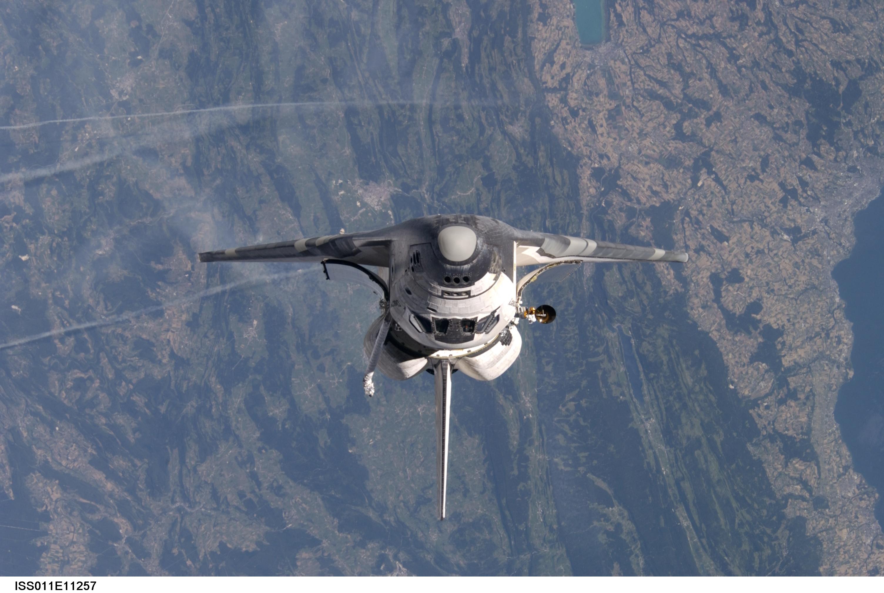 Photo de la navette spatiale Discovery prise depuis ISS. On distingue en arrière plan Pontarlier, le Lac Saint Point, une petite partie du lac Léman